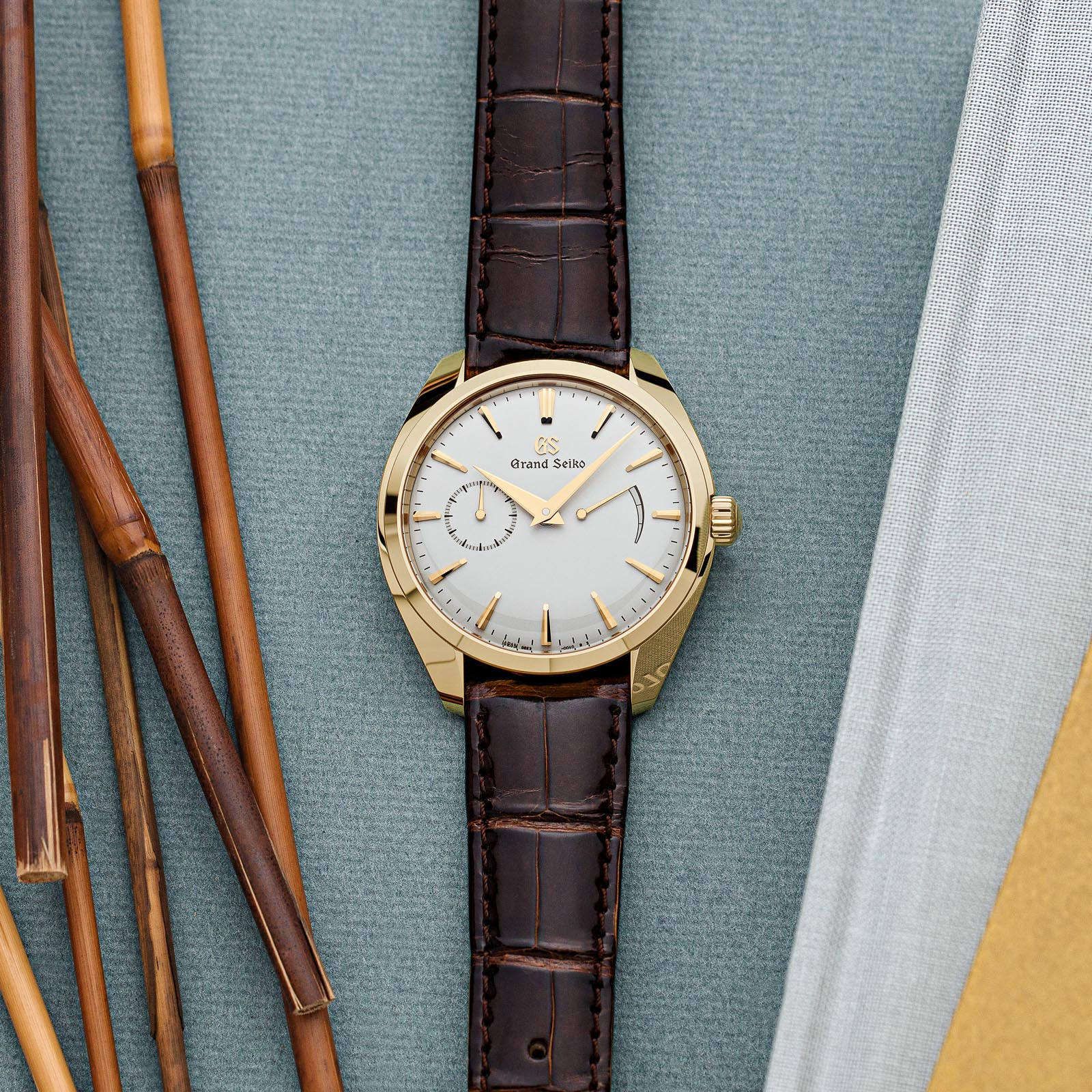A slim, yellow gold Grand Seiko timepiece with a light dial and brown strap.