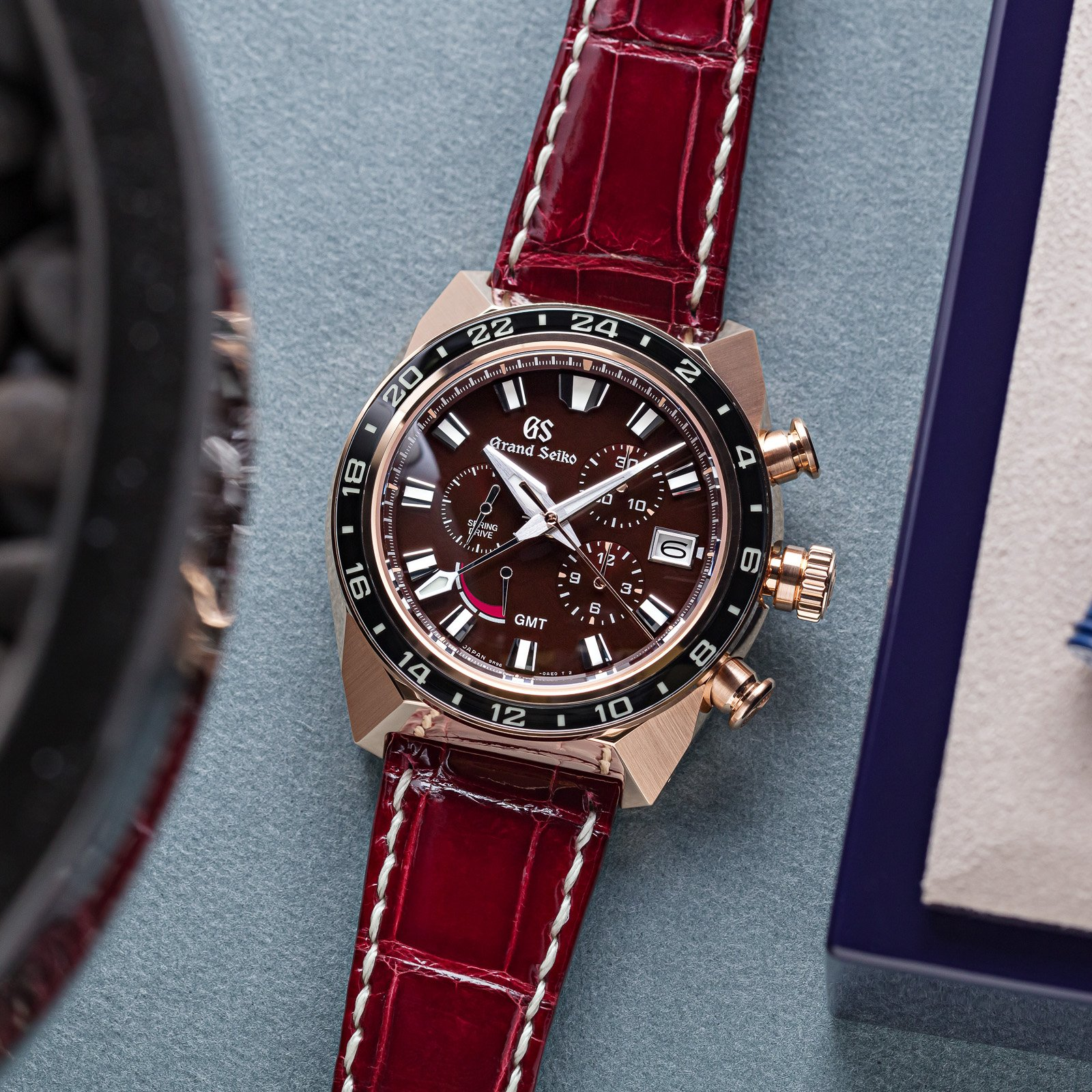 Grand Seiko Chronograph SBGC230 - gold-cased wristwatch with a red textured dial and leather strap.