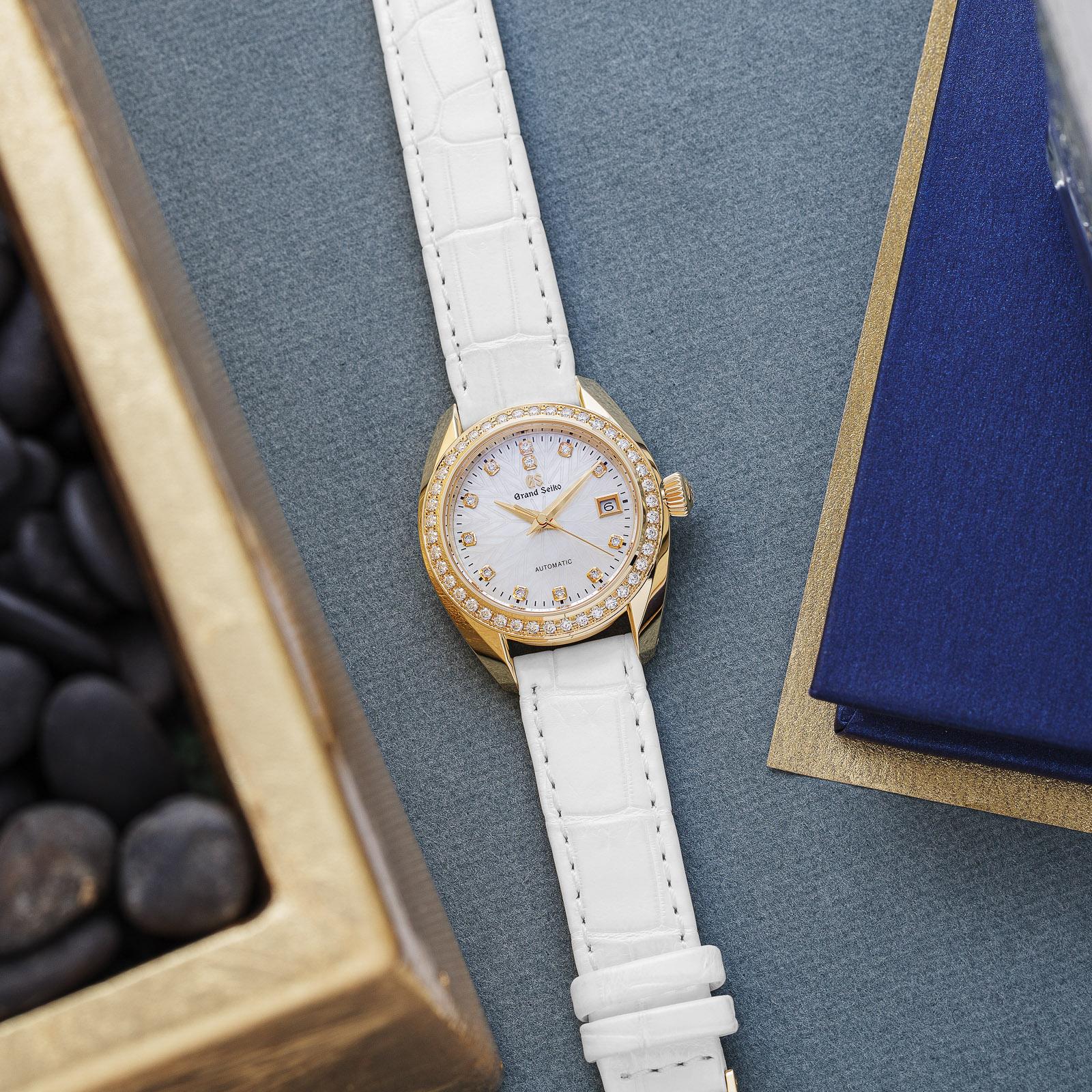 Grand Seiko wristwatch STGK004 - white dial, gold case on a white strap atop a table.
