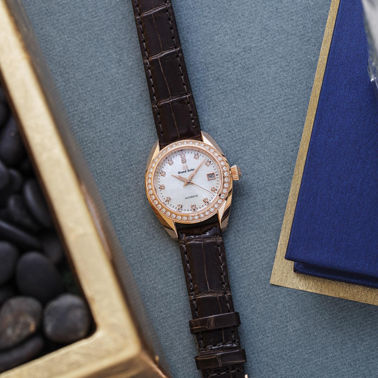 Grand Seiko wristwatch STGK006 - white dial, gold case on a brown strap atop a table.