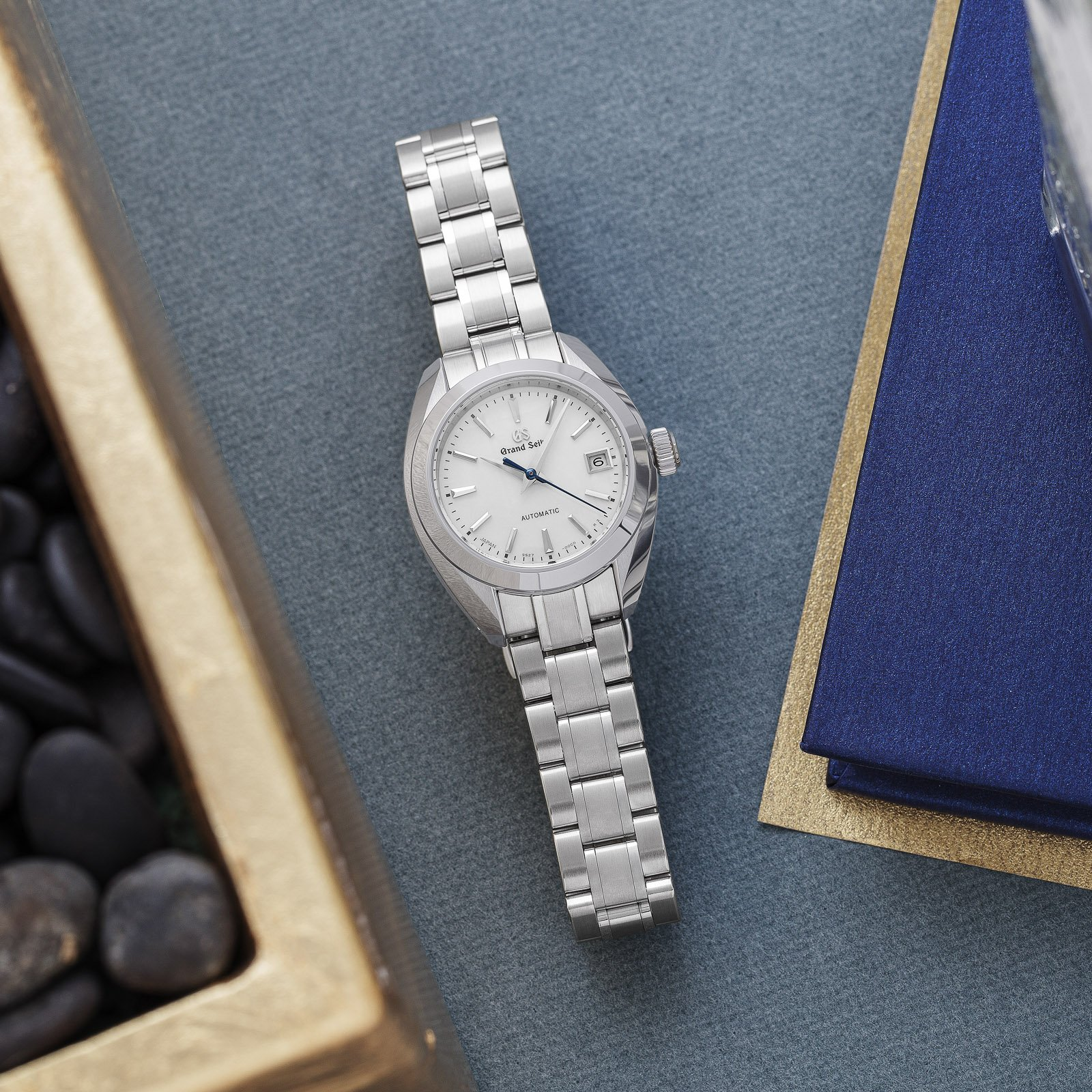 Grand Seiko model STGK009 - wristwatch with a white dial and stainless steel case atop a table.