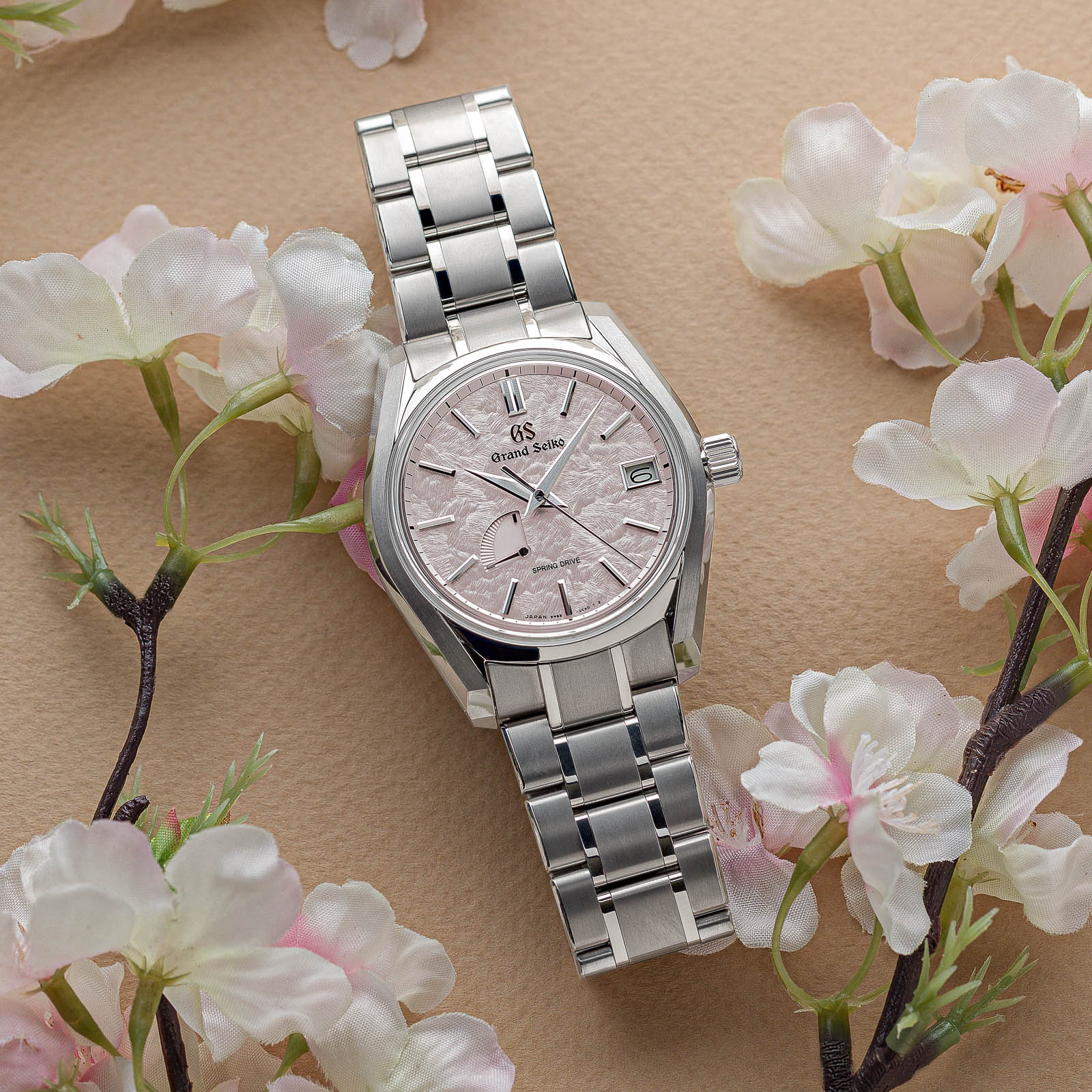 A pink dial Grand Seiko wristwatch in a titanium case with matching bracelet.