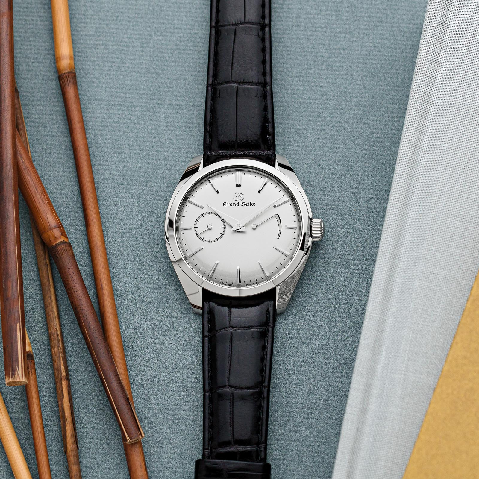 Grand Seiko stainless steel dress watch with a light dial and black crocodile strap.