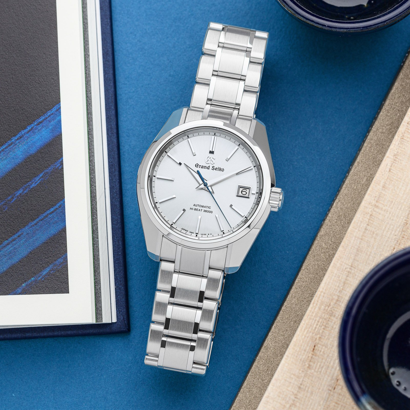 White dial stainless steel wristwatch atop a blue table.