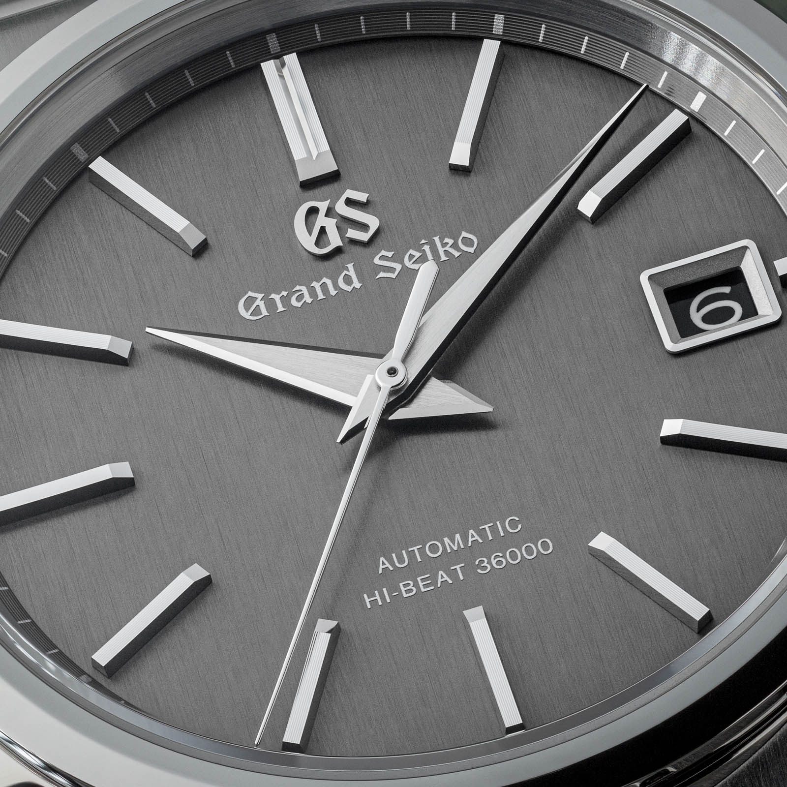 Closeup of a dark gray watch dial.