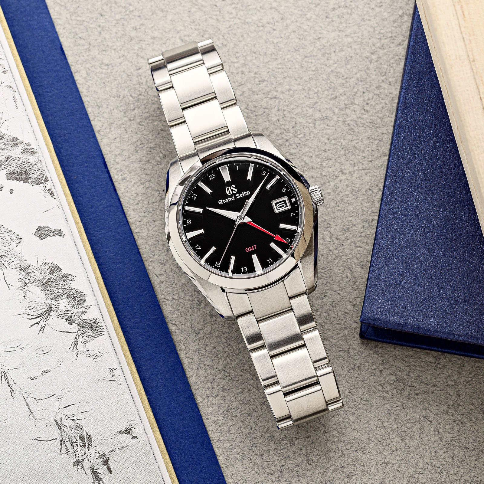 A black dial stainless steel wristwatch with red dial accents atop a table.