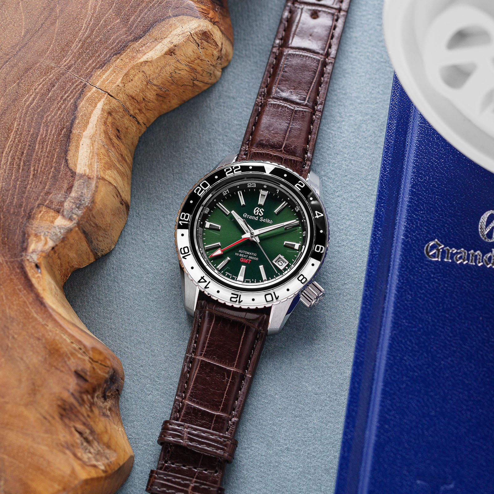 Grand Seiko SBGJ239 - green dial stainless steel wristwatch with a two-tone bezel and leather strap atop a table.