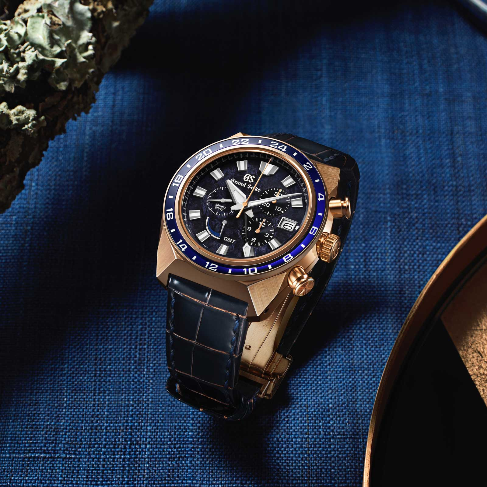 Grand Seiko SBGC238 - blue dial chronograph in gold case on blue tabletop.