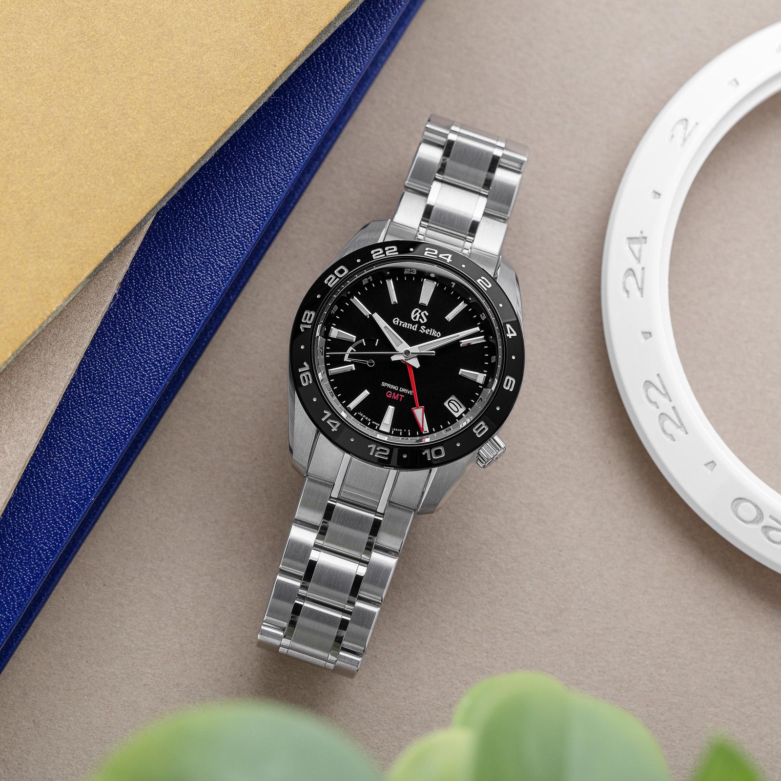 Grand Seiko SBGE253- a black dial, black ceramic bezel wristwatch on bracelet.