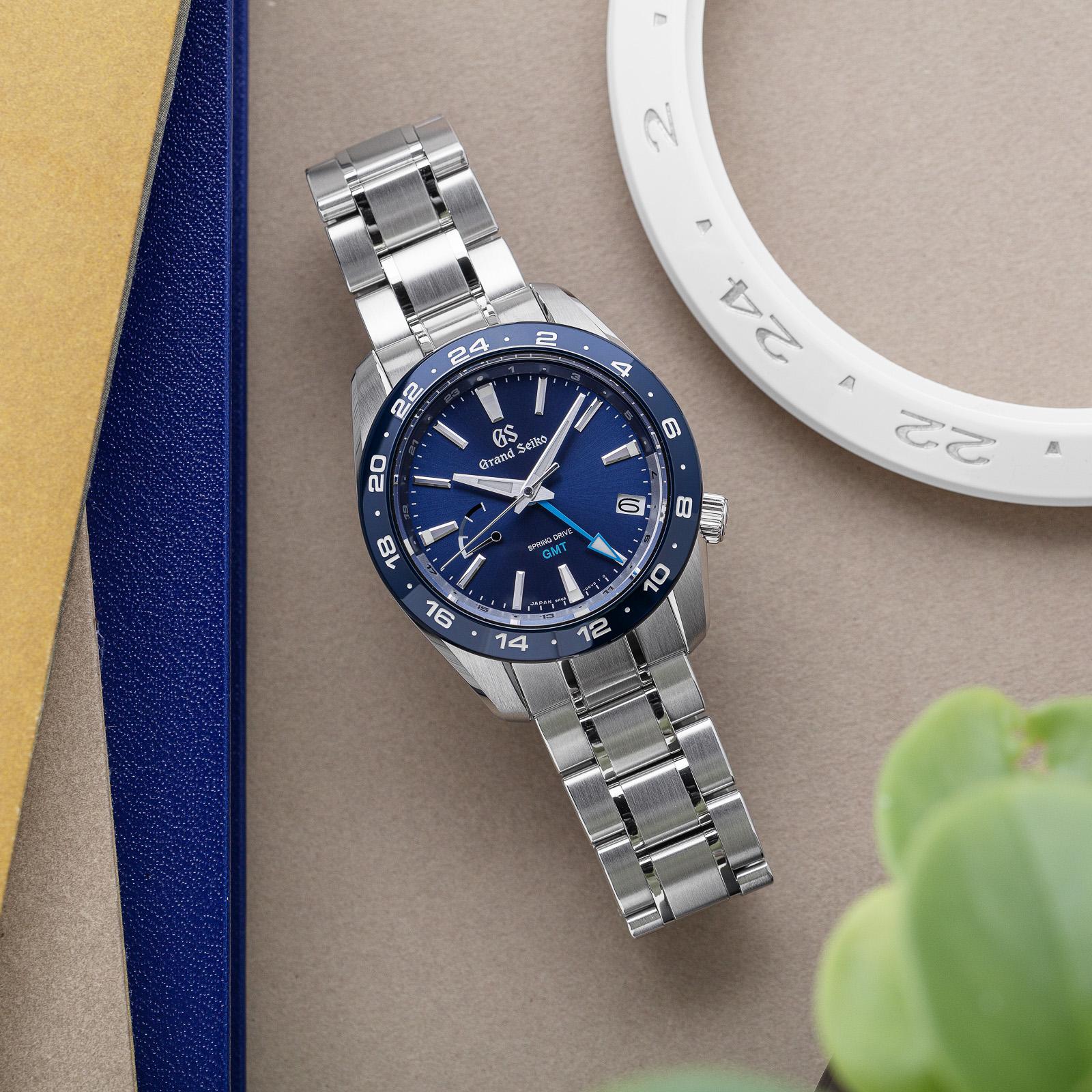 Grand Seiko SBGE255- a blue dial, blue ceramic bezel wristwatch on bracelet.