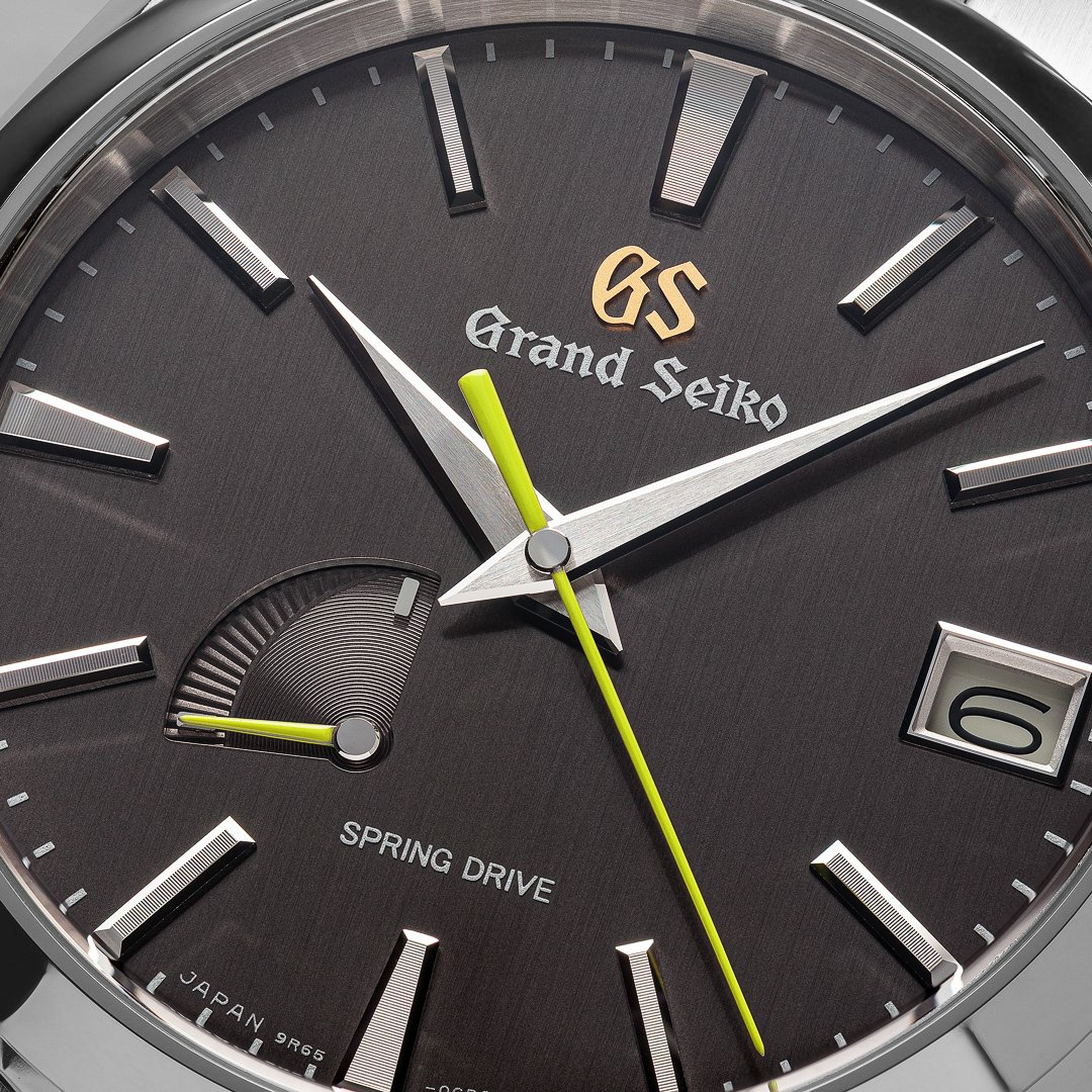 Close up of a dark dial wristwatch with green accents.