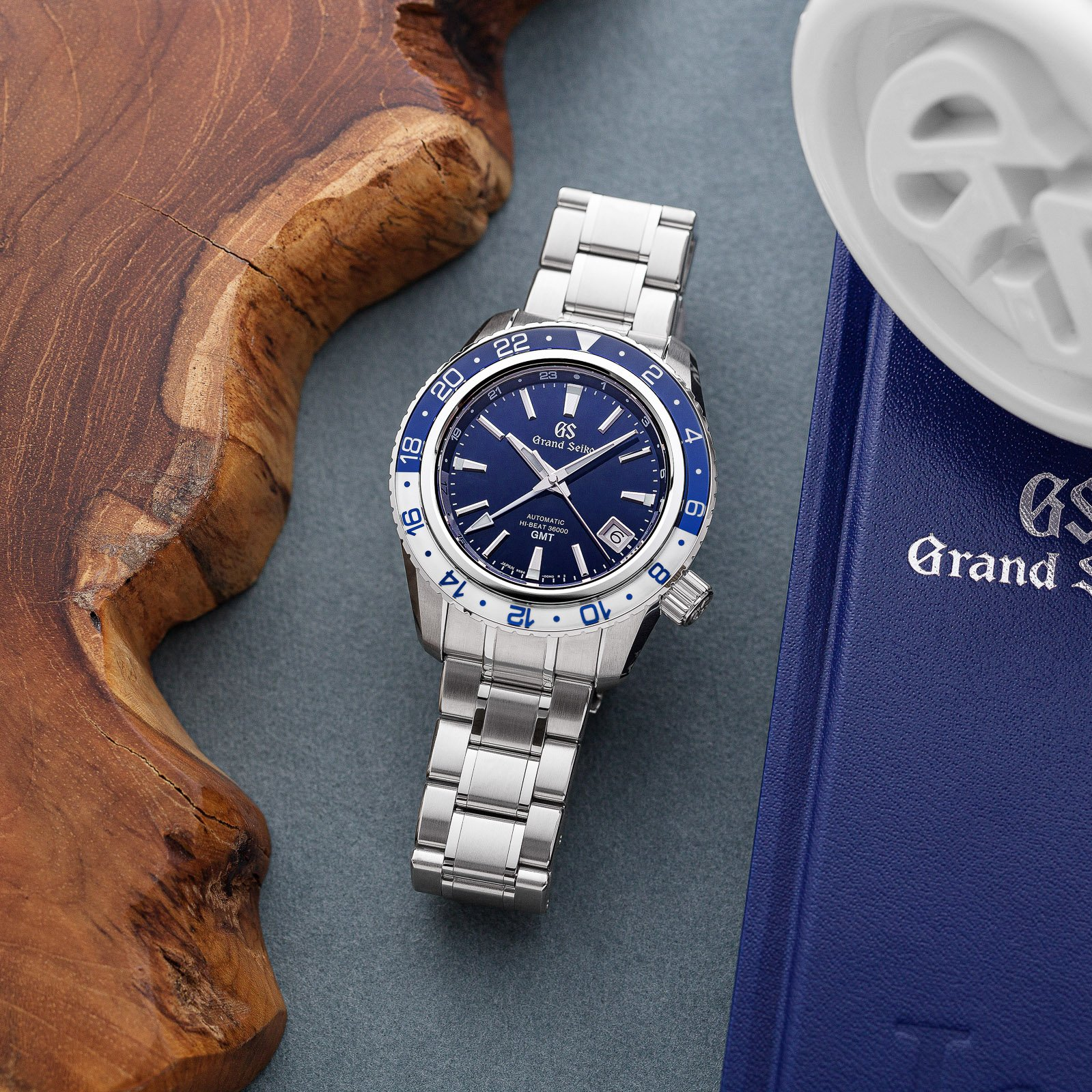 Grand Seiko SBGJ237 - blue dial stainless steel wristwatch with a two-tone bezel atop a table.