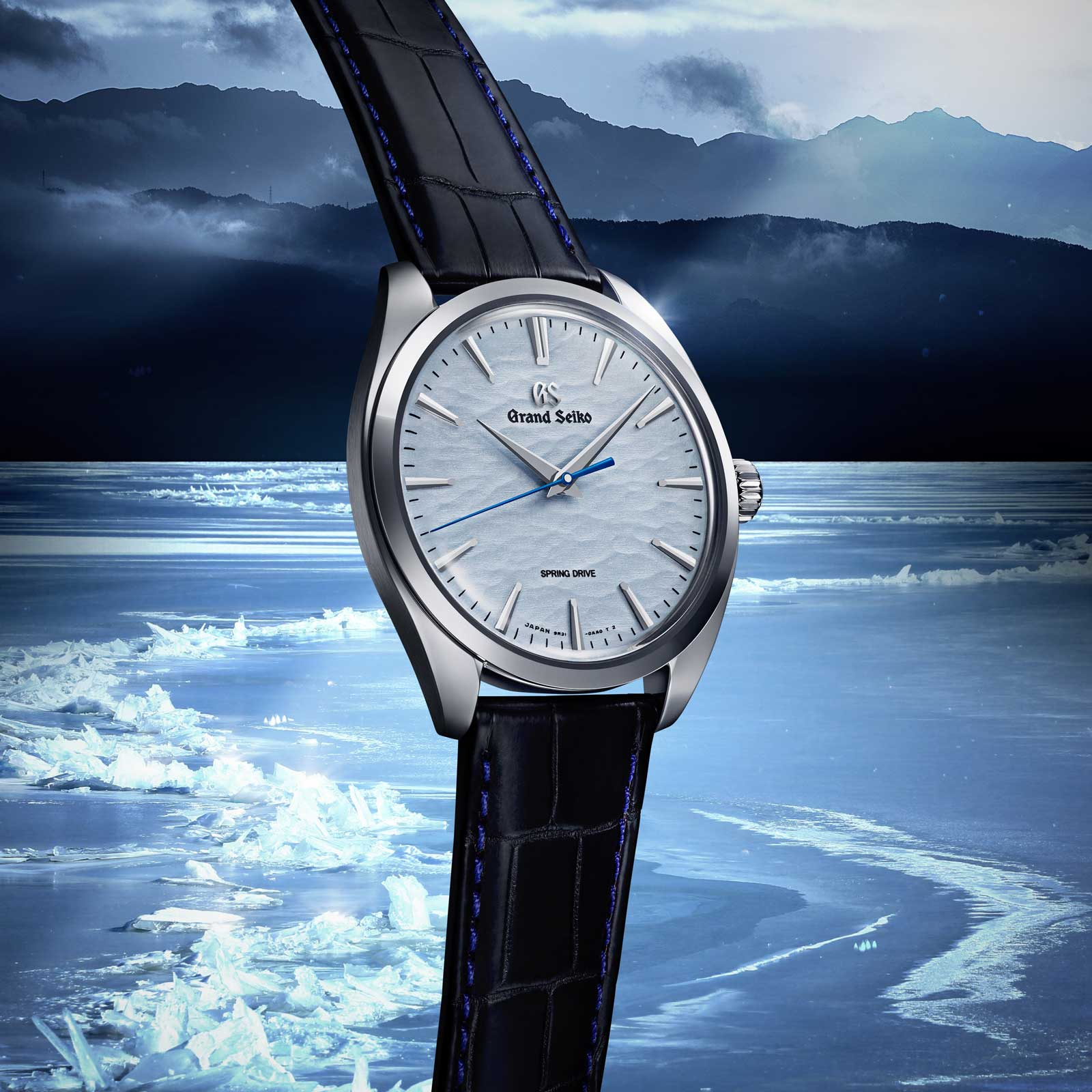 Grand Seiko SBGY007 - blue dial wristwatch in a stainless steel case against frozen lake background.