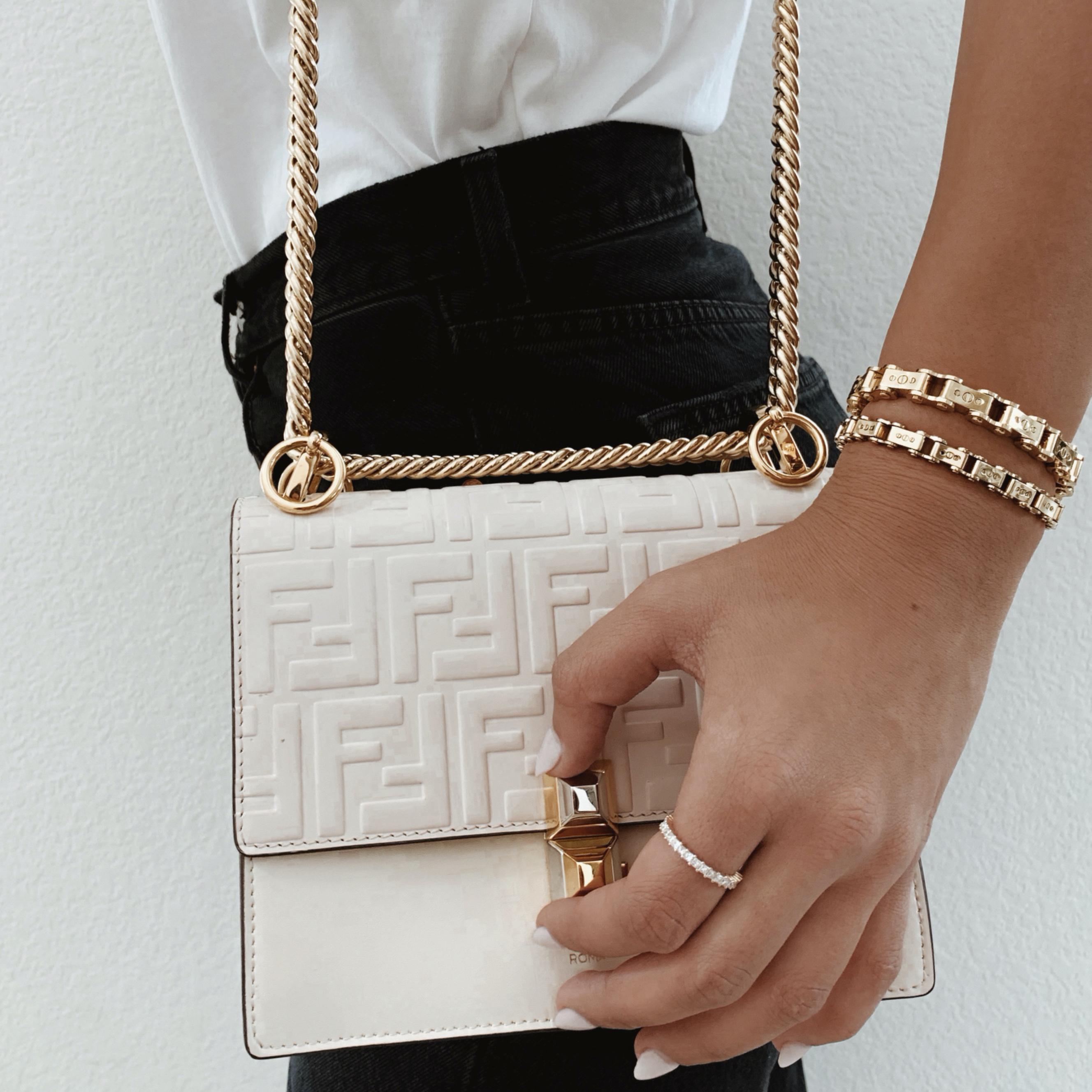 Women's Gold 9.5mm Bicycle Bracelet next to handbag