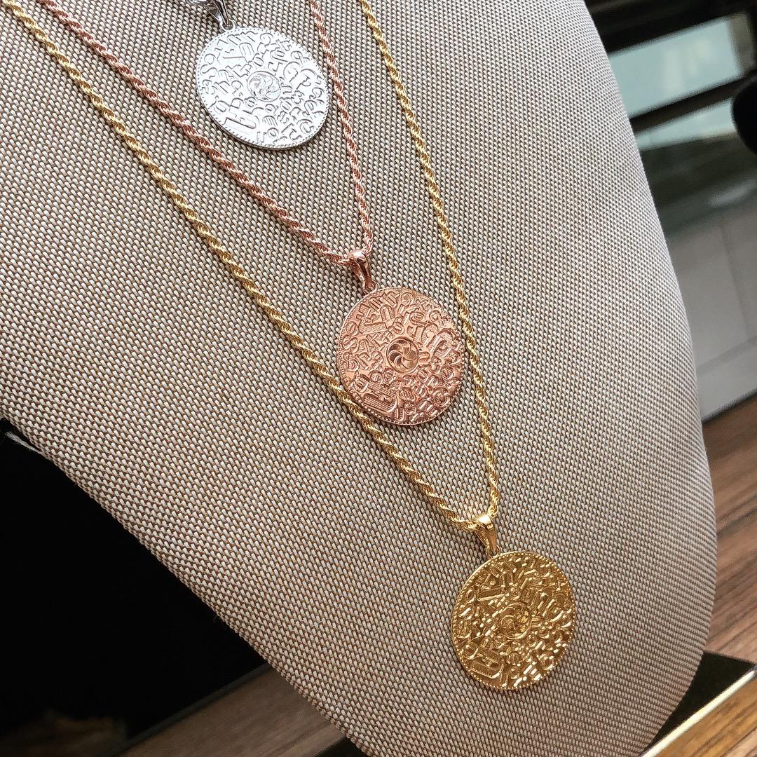 Rose Gold Armenian Alphabet Necklace on display
