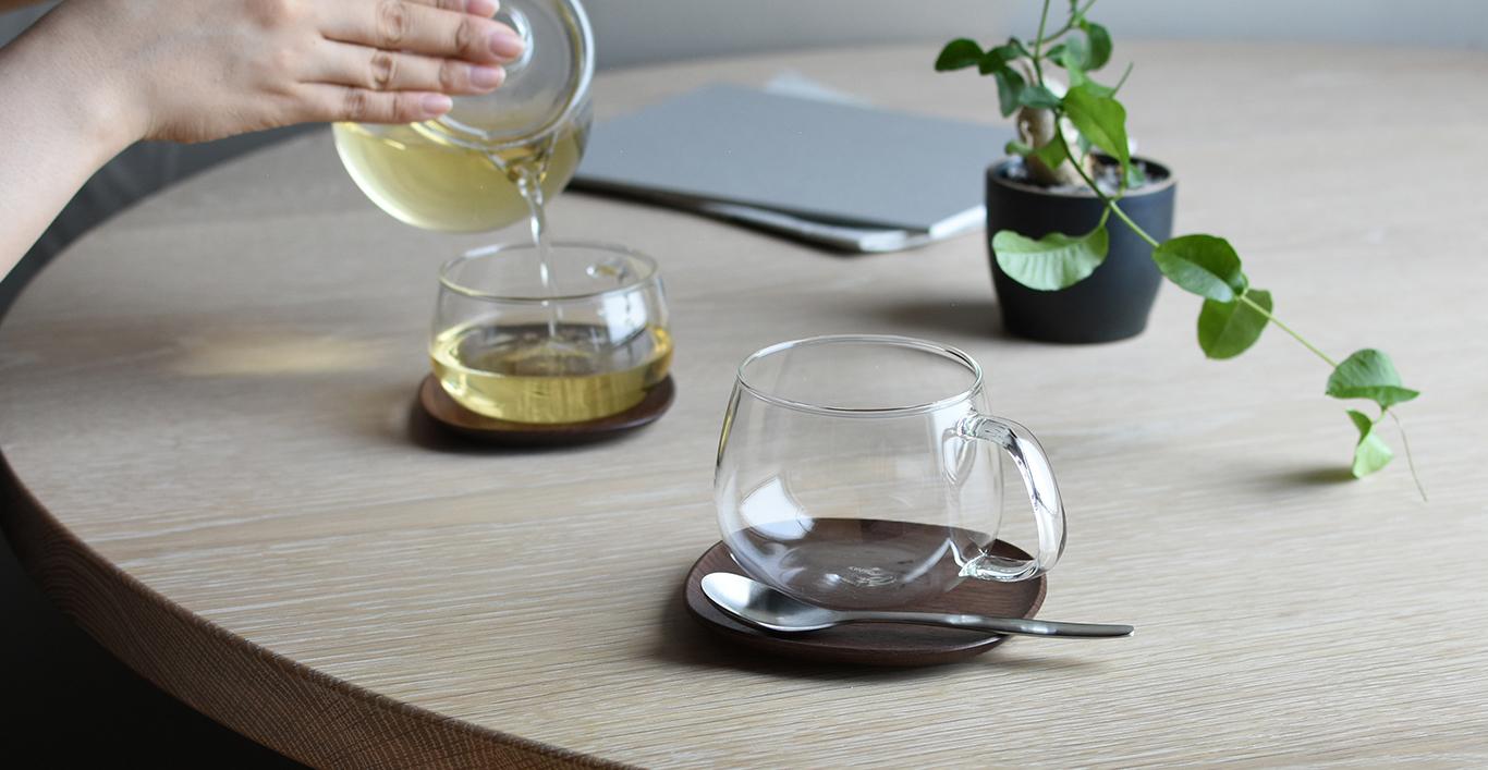 Tea being poured with the UNITEA teapot into UNITEA cups on a UNITEA walnut coaster