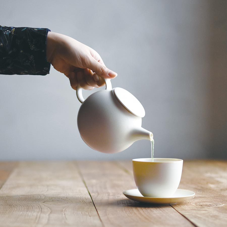 Pouring tea with PEBBLE teapot into PEBBLE cup and saucer