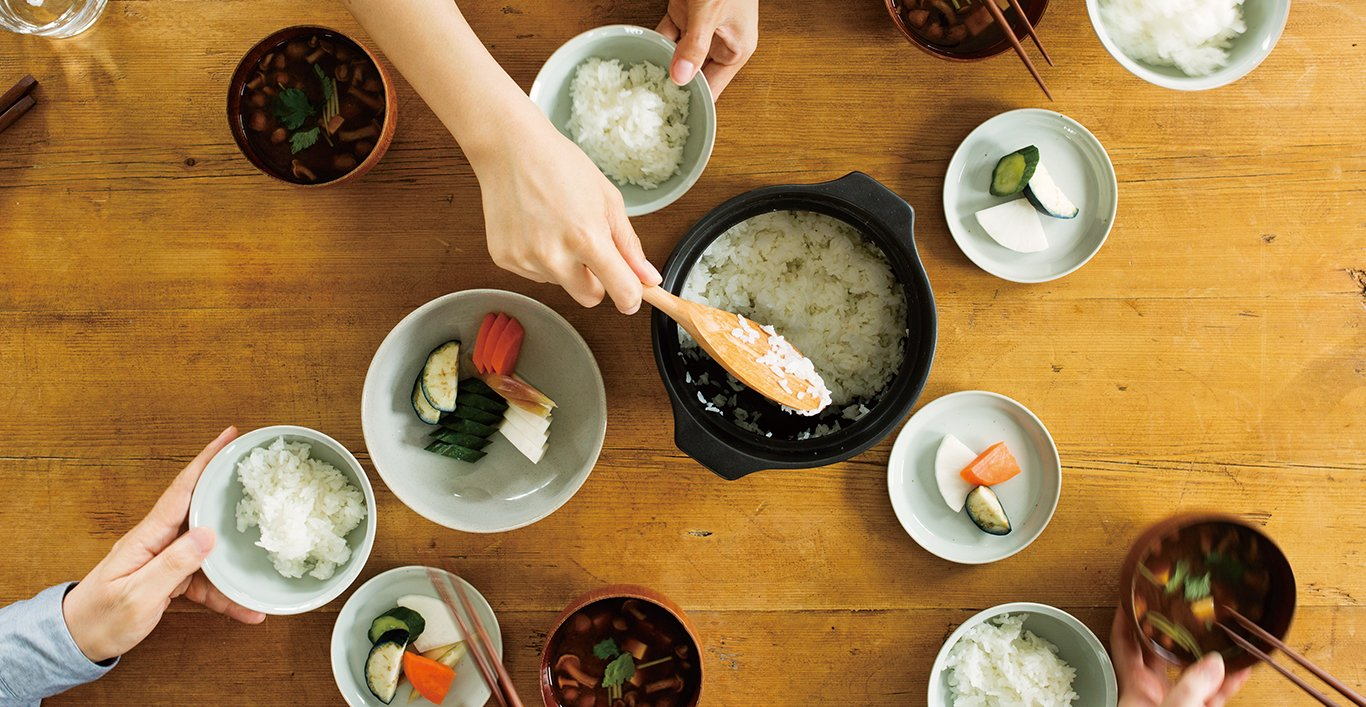 Scooping rice out of the KAKOMI rice cooker with various tableware with food