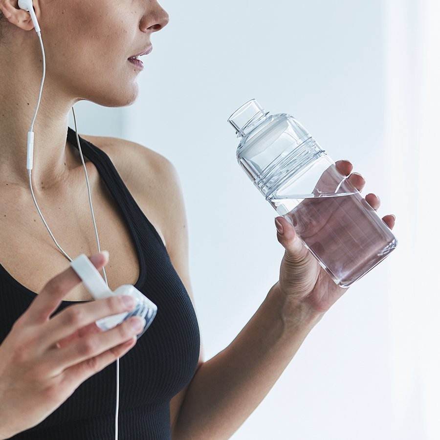 WORKOUT bottle clear being used by a person in exercise apparel
